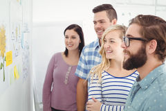 Smiling business people looking at wall with sticky notes and drawings Stock Image