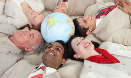 Smiling business people lying around a globe. Smiling business people lying in a circle around a globe Royalty Free Stock Photo