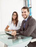 Smiling business people at office desk Royalty Free Stock Images