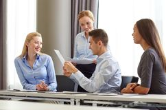 Smiling business people with papers in office Stock Photos