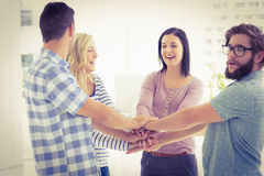 Smiling business people putting their hands together Royalty Free Stock Image