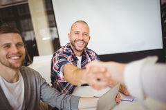 Smiling business people shaking hands in office Stock Photos