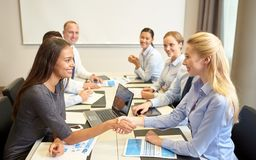 Smiling business people shaking hands in office Stock Photography
