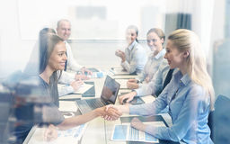 Smiling business people shaking hands in office Royalty Free Stock Photos