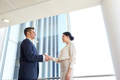 Smiling business people shaking hands at office Royalty Free Stock Photo