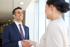 Smiling business people shaking hands at office Stock Images