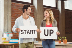 Smiling business people showing card with start up text in office Stock Photo