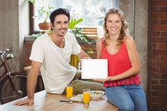 Smiling business people showing digital tablet in office Royalty Free Stock Image