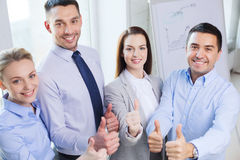 Smiling business people showing thumbs up Royalty Free Stock Photos