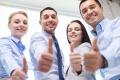 Smiling business people showing thumbs up Stock Photography