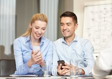 Smiling business people with smartphones in office Royalty Free Stock Photos