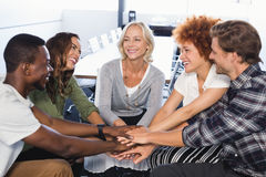 Smiling business people stacking hands while sitting on chairs. In office Stock Photography