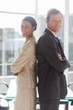 Smiling business people standing back to back Stock Images