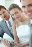 Smiling business people standing in hallway using tablet Royalty Free Stock Image