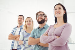 Smiling business people standing in row with arms crossed Stock Images