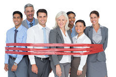 Smiling business people surrounding by red strip Stock Photography