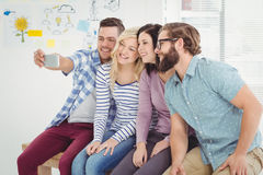 Smiling business people taking self portrait on smartphone Stock Image