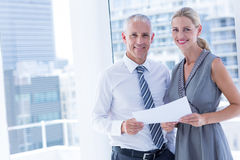 Smiling business people talking over a paper sheet Royalty Free Stock Photos