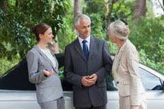 Smiling business people talking together by classy cabriolet. On a bright day Stock Images