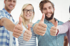 Smiling business people with thumbs up. While standing at office Stock Photos