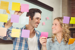 Smiling business people touching sticky notes on glass in office Royalty Free Stock Image
