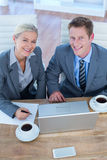 Smiling business people using laptop Stock Photo