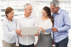 Smiling business people using laptop Stock Image