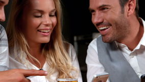 Smiling business people using smartphone. In bar stock footage