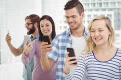 Smiling business people using smartphones while standing in row Stock Photo