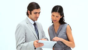 Smiling business people using a tablet computer. Against a white background stock footage