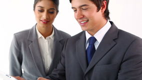 Smiling business people using a tablet pc. Against a white background stock footage