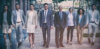Smiling business people walking outside office. Portrait of smiling business people walking outside office building stock photo