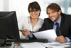 Smiling business people working. Two business people behind a monitor smiling at camera Stock Image