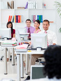 Smiling business people working at computers Royalty Free Stock Image