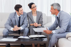Smiling business people working and talking together on sofa Stock Image