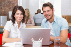 Smiling business people working together with laptop. In the office Stock Photography
