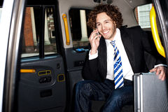 Smiling business person communicating. Handsome cheerful male passenger communicating through mobile phone Stock Photography