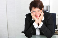 Smiling business professional at her desk Royalty Free Stock Photography