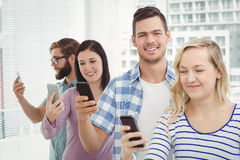 Smiling business professionals using smartphones while standing in row Stock Photos
