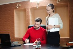 Smiling business specialist and secretary working in office stock image