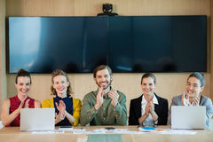 Smiling business team applauding during meeting in conference room. Portrait of smiling business team applauding during meeting in conference room at office Stock Photography