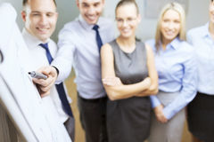 Smiling business team with charts on flip board Royalty Free Stock Photography
