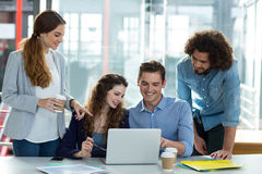 Smiling business team discussing over laptop in meeting Royalty Free Stock Photo