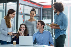 Smiling business team discussing over laptop in meeting Royalty Free Stock Photography