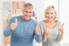 Smiling business team gesturing thumbs up Stock Images