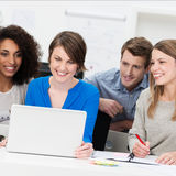 Smiling business team grouped around a laptop Royalty Free Stock Images