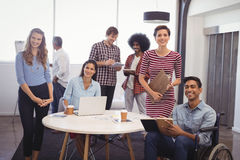 Smiling business team with handicap colleague in creative office. Portrait of smiling business team with handicap colleague in creative office Stock Photography