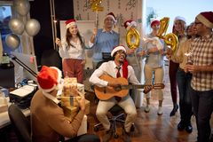 Smiling business team have fun and dancing in Santa hat at Xmas party stock photography