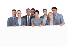 Smiling business team holding poster Stock Images