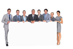 Smiling business team holding poster Royalty Free Stock Photos